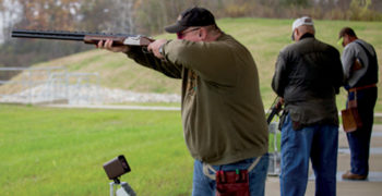 Three shooting event attendees on the shotgun range.