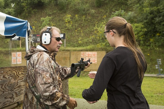 Instructor teaching proper gun handling to student.