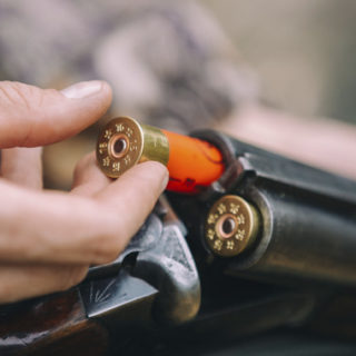 Closeup of an individual loading a shotgun.